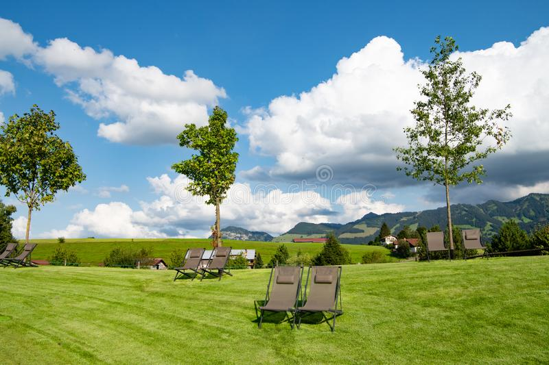 Large fluffy white clouds over meadow with deck chairs in landscape of Allgau, German Alps, royalty free stock photos