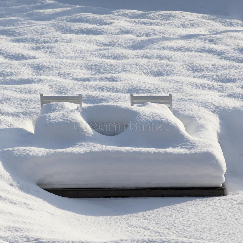 Deckchairs with towering snow. Garden patio snowed under. stock photography