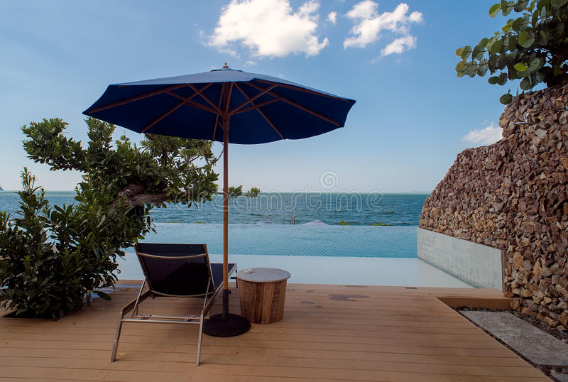 Deck chairs with umbrella overlooking infinity pool and tropical stock photography