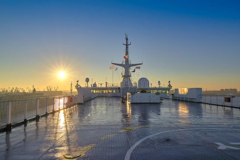 Deck of a cruise liner setting at the port against the background of the morning rising sun. Early morning stock photography