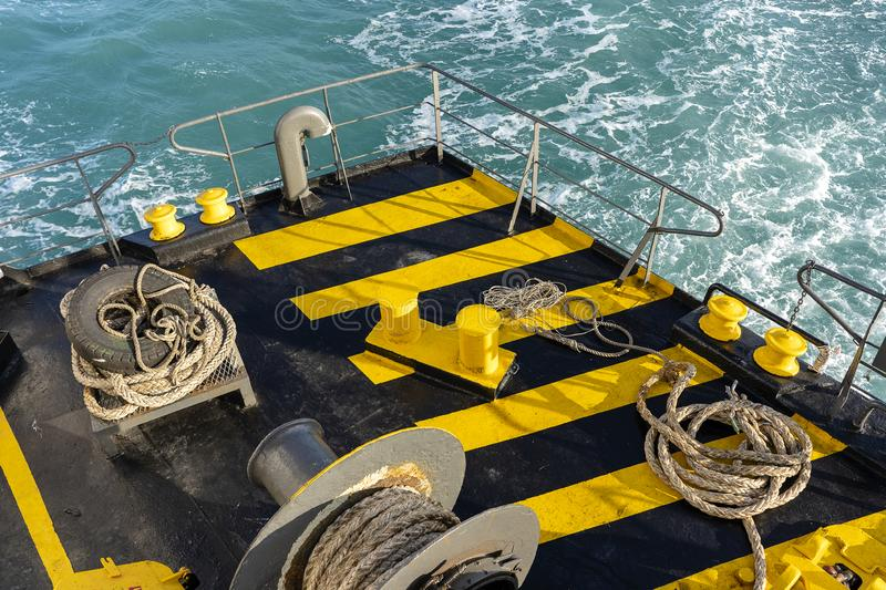 The deck of the ferry boat along with the a thick mooring rope and blue sea water wave, Thailand. Close up royalty free stock photos
