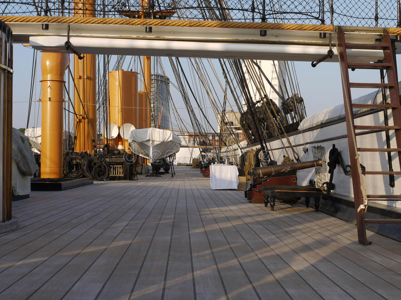 Deck of HMS Warrior,. Wooden deck of HMS Warrior in afternoon sunshine with stairs, cannon, lifeboat and stack stock photography