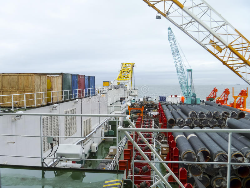The deck lay barge. Pipes and Lifting cranes on the ship. Equipment for laying a pipeline on the seabed stock photography