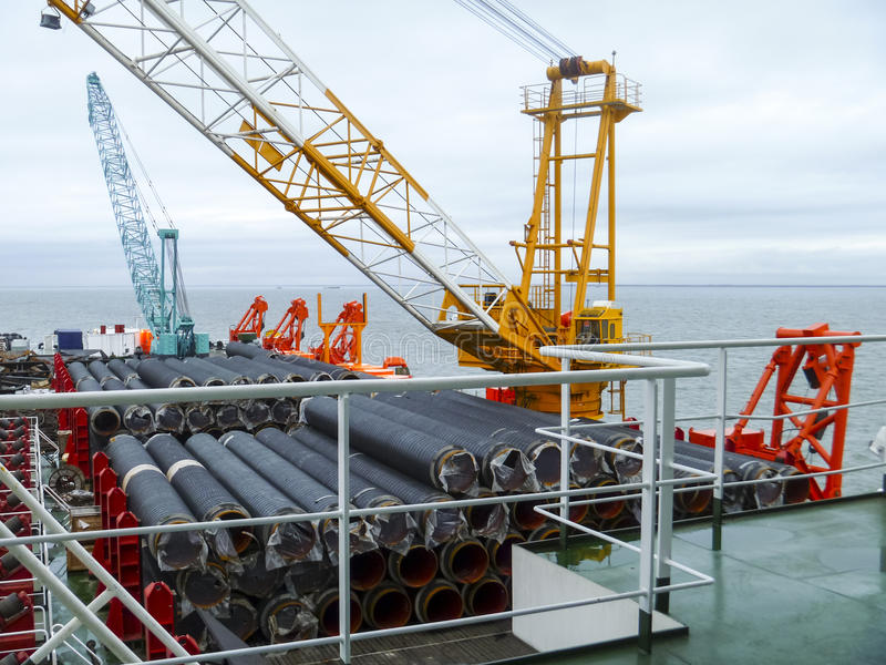 The deck lay barge. Pipes and Lifting cranes on the ship. Equipment for laying a pipeline on the seabed royalty free stock images