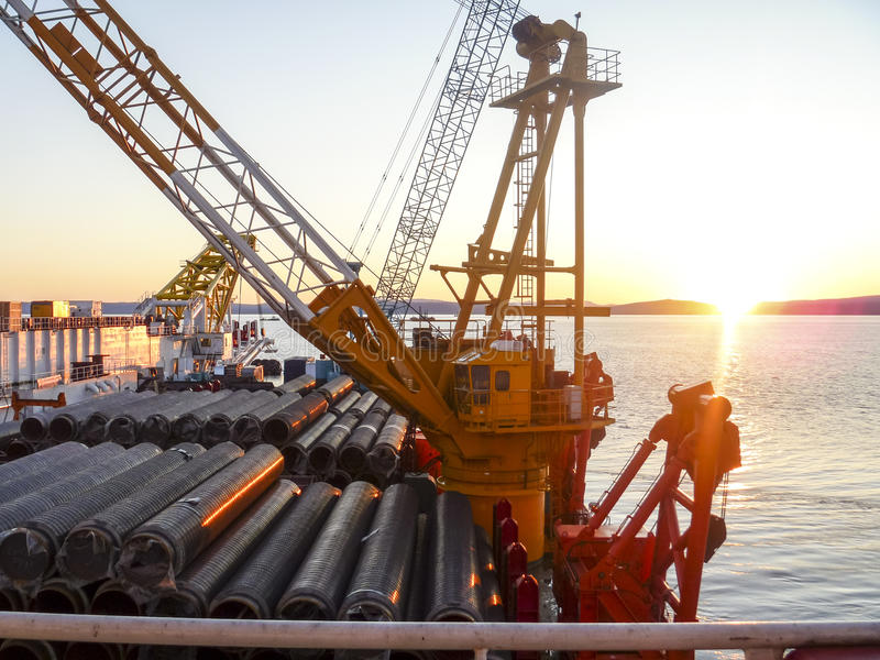 The deck lay barge. Pipes and Lifting cranes on the ship. Equipment for laying a pipeline on the seabed stock image