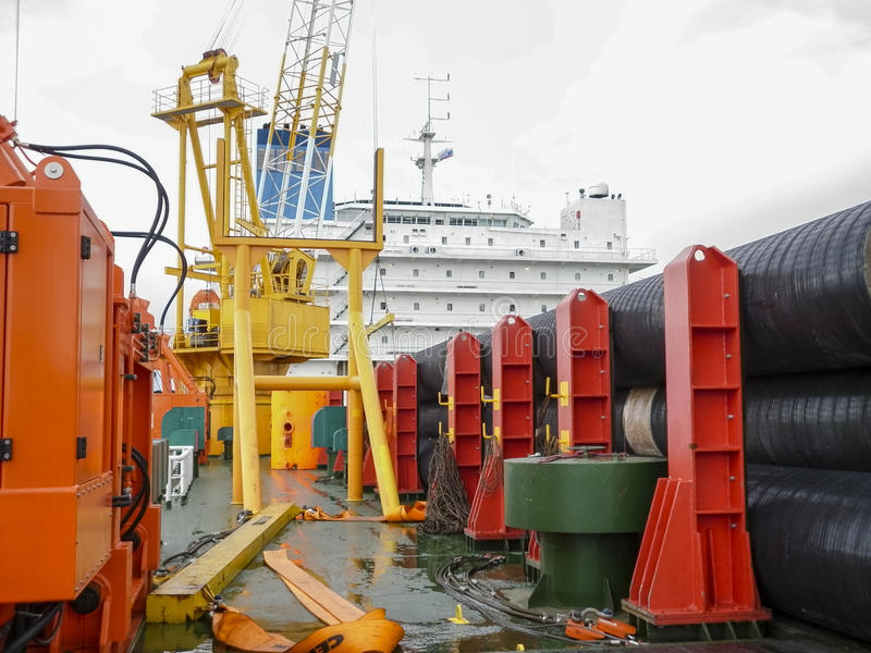 The deck lay barge. Pipes and Lifting cranes on the ship. Equipment for laying a pipeline on the seabed royalty free stock photography
