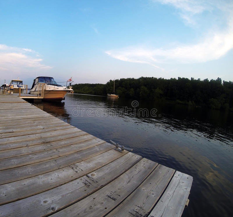 On Deck Looking at Boats. On a wood deck, looking at boats on a river near Trois-Rivieres, Quebec, Canada. Beautiful blue sky with clouds royalty free stock image