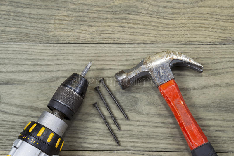 Deck Materials. Power screwdriver, wood screws and hammer lying on faded wooden Deck boards royalty free stock images