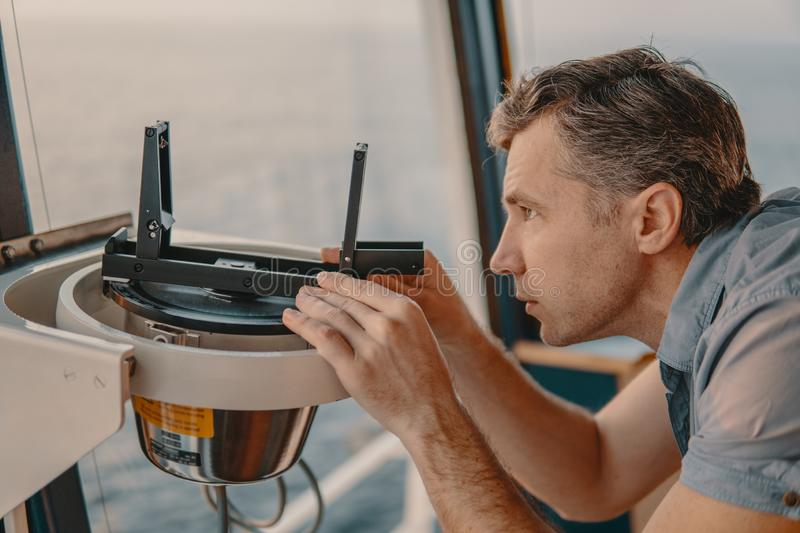 Deck officer taking magnetic compass error onboard of vessel. Marine deck officer taking magnetic compass error onboard of vessel at open sea. Job at sea stock images