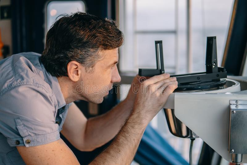 Deck officer taking magnetic compass error onboard of vessel. Marine deck officer taking magnetic compass error onboard of vessel at open sea. Job at sea stock photography