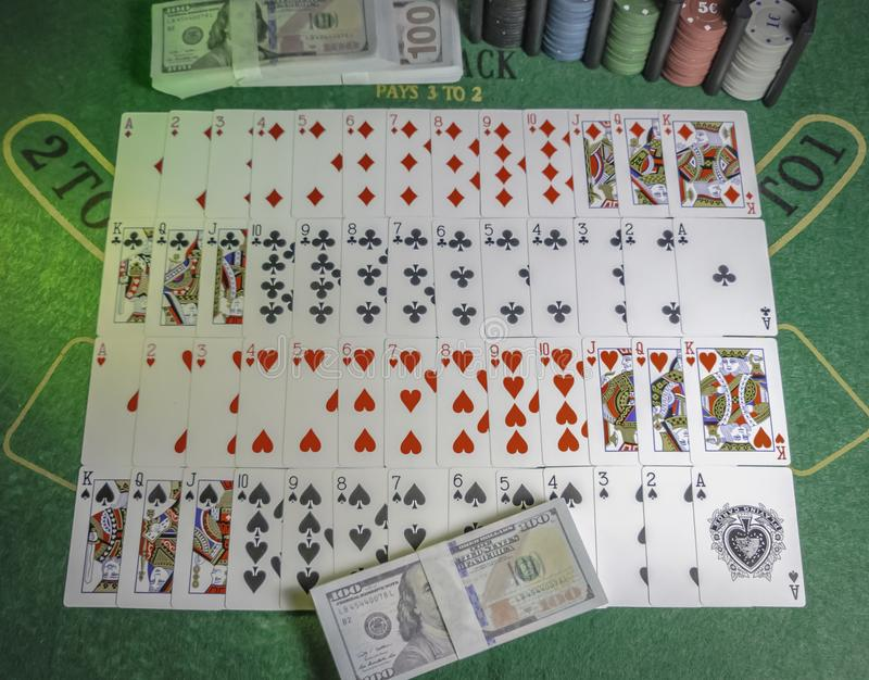Deck of playing cards, Casino chips and pack of 100s of US dollars on the green table for Blackjack lighted with party lights royalty free stock image