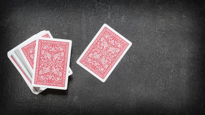 Deck of playing cards and one card separately face down on a black table. Top view stock image