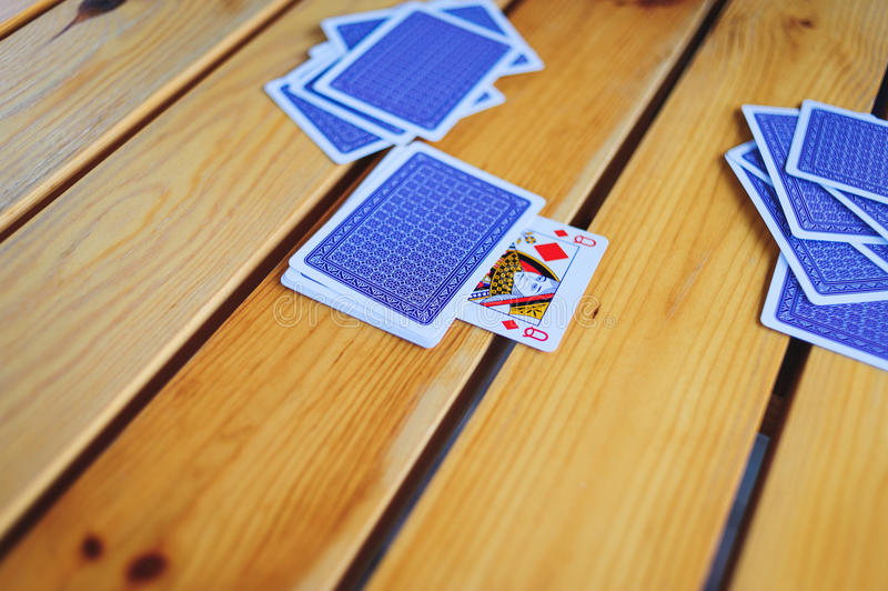 Deck of playing cards on a wooden table pile with an open trump card of a diamond lady. royalty free stock photography