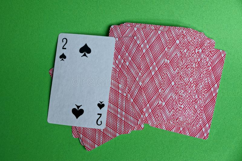A deck of red cards with a peak deuce on a green table stock photos