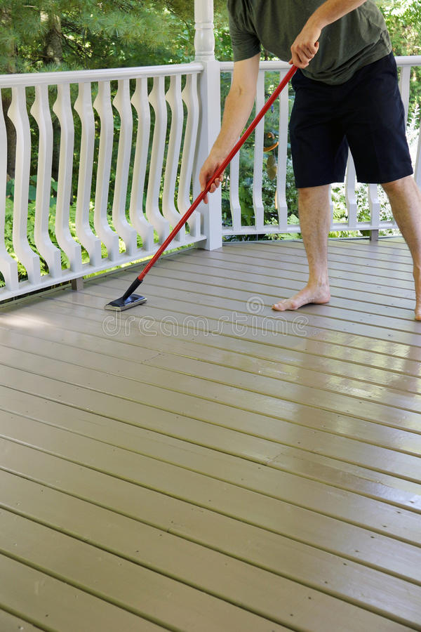 Deck Staining. A wooden deck gets a fresh coat of solid stain with a staining pad royalty free stock image