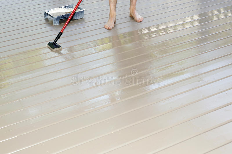 Deck Staining. A wooden deck gets a fresh coat of solid stain with a staining pad royalty free stock photo