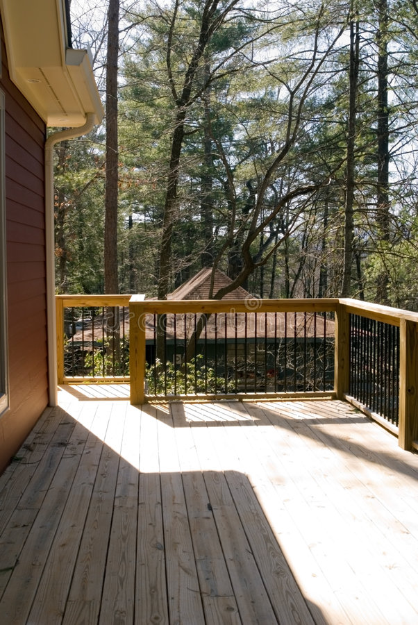 Deck With Wood and Metal Rails. Wood deck with metal rails on back of red house, another house in the distance royalty free stock photo