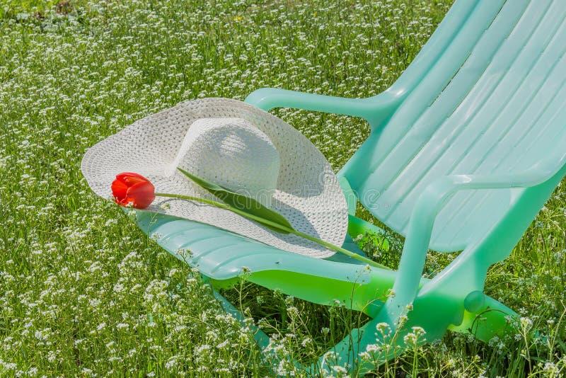 Deckchair、郁金香和帽子在庭院里 库存照片