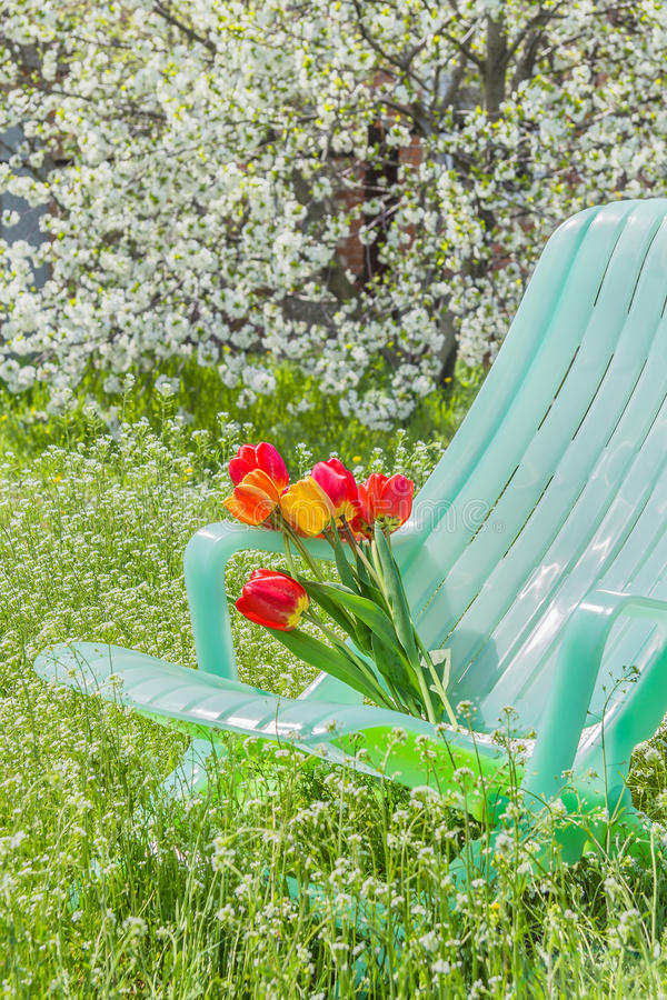 Deckchair和郁金香花束在庭院里 免版税库存图片