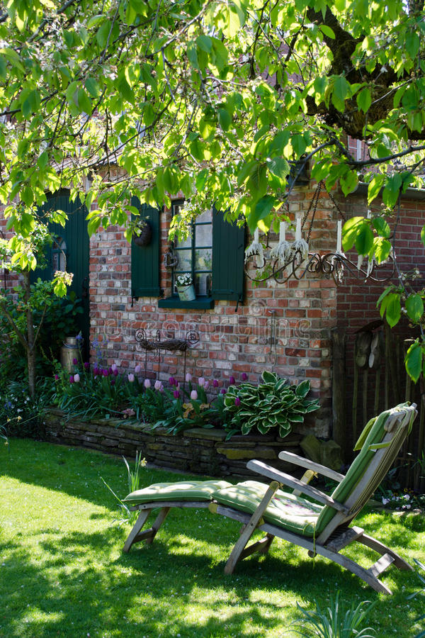 Deckchair在一个舒适庭院里 库存照片