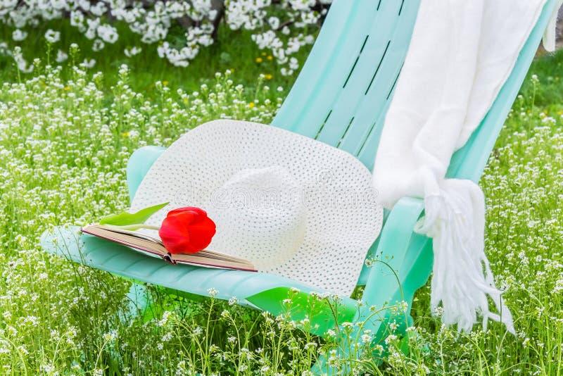 Deckchair,郁金香 围巾和帽子在庭院里 图库摄影