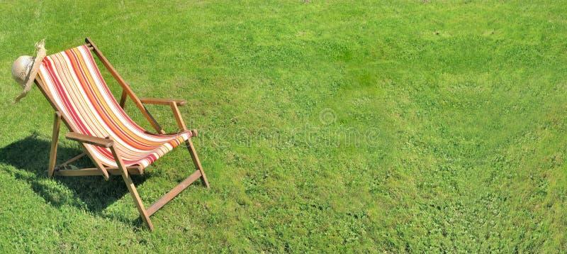 Deckchair в траве сада стоковые изображения