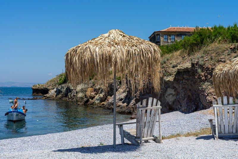 Deckchair и зонтик сделанный из соломы на каменистом пляже стоковое фото