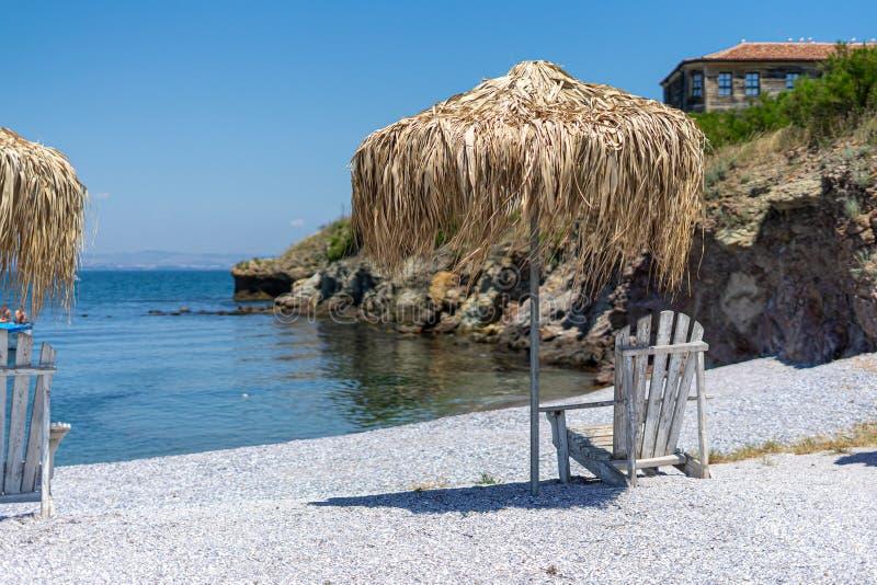 Deckchair и зонтик сделанный из соломы на каменистом пляже стоковое изображение
