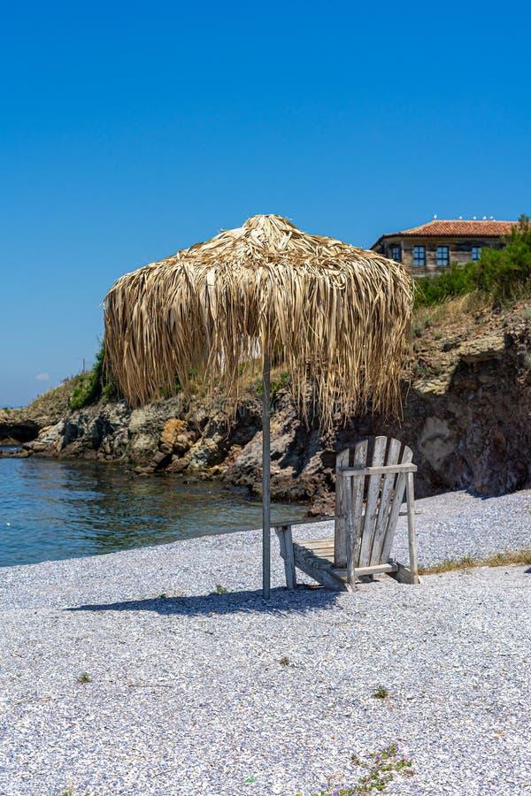 Deckchair и зонтик сделанный из соломы на каменистом пляже стоковые изображения