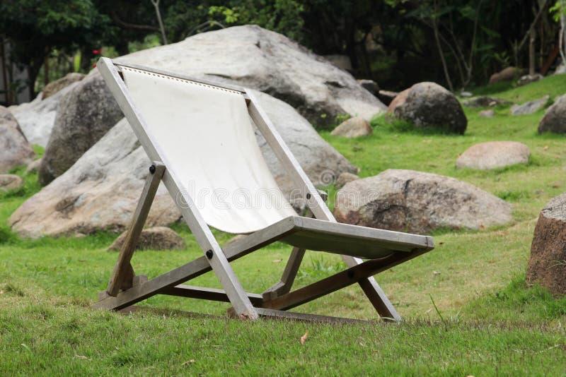 Deckchair на зеленой траве стоковая фотография rf