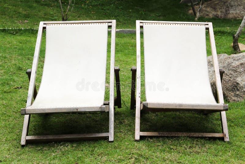 Deckchair на зеленой траве стоковые изображения rf