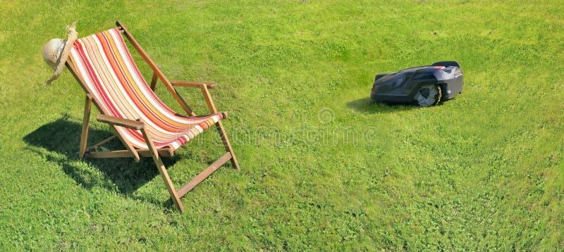 Deckchair на траве растительности и робототехнической травокосилке стоковое изображение rf