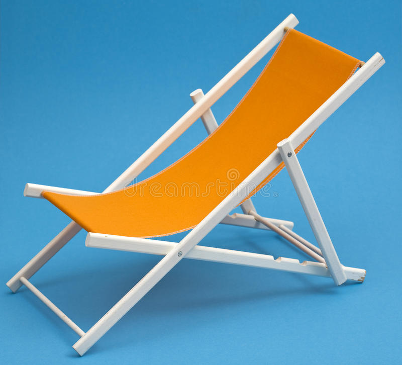 Deckchair. Orange deckchair on sky blue background stock images