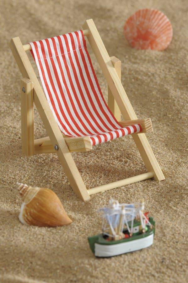 Deckchair alla spiaggia piena di sole fotografia stock