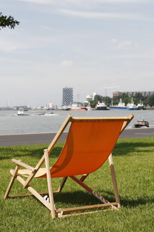 Deckchair arancione in erba con la vista sul fiume occupato fotografia stock libera da diritti