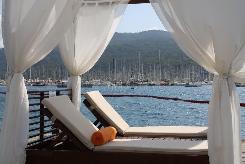 Deckchair auf der Bucht lizenzfreie stockfotografie