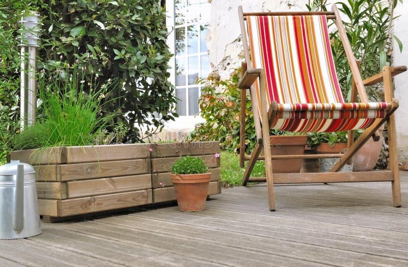 Deckchair auf hölzerner Terrasse lizenzfreies stockbild