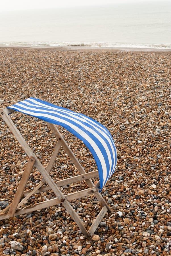 Deckchair auf windigem Strand lizenzfreie stockbilder