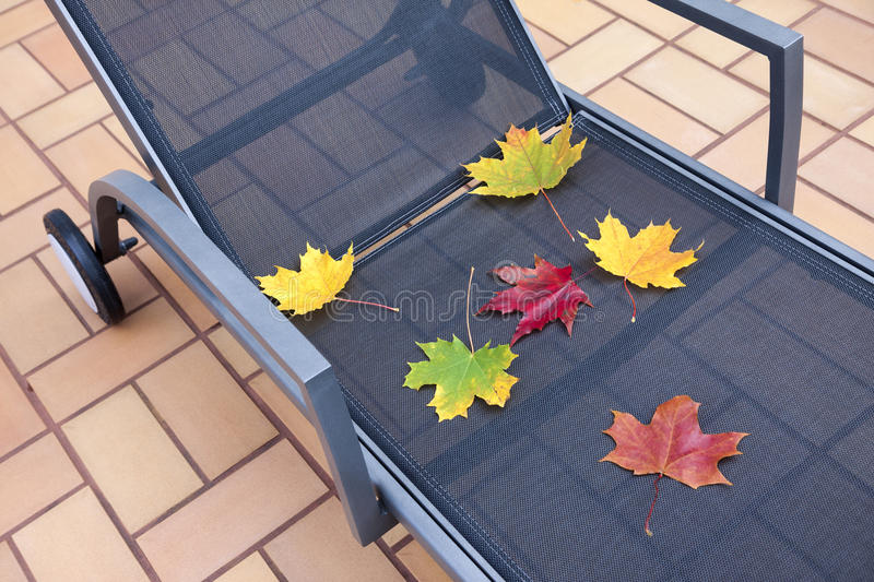 Deckchair at autumn. Part of terrace deckchair with maple leaves at fall royalty free stock photography