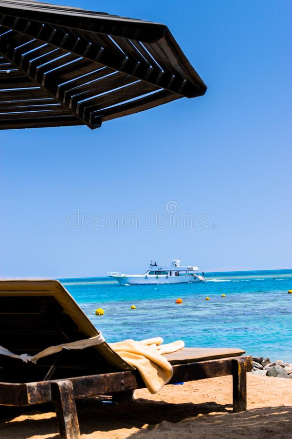 Deckchair on the beach and the ship sails. Deckchair under a sun umbrella on the beach. The yacht is sailing. Steigenberger Aqua Magic Hotel in Hurghada, Egypt stock photos