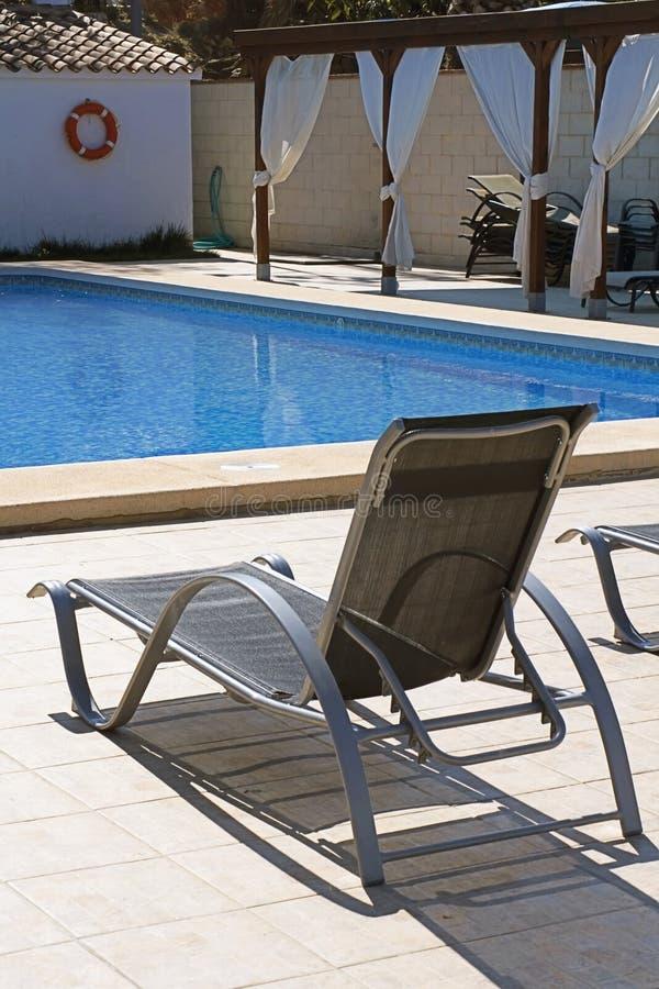 Deckchair cerca de una piscina fotos de archivo