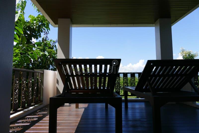Deckchair de madeira no balcão com opinião da floresta e do céu imagem de stock royalty free