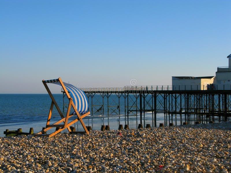Deckchair durch den Pier lizenzfreie stockbilder