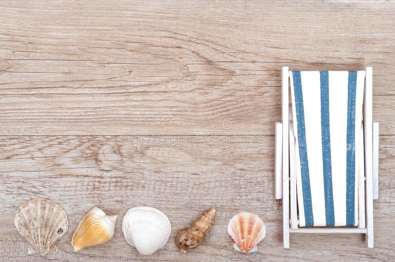 Deckchair e escudos do mar na madeira imagem de stock