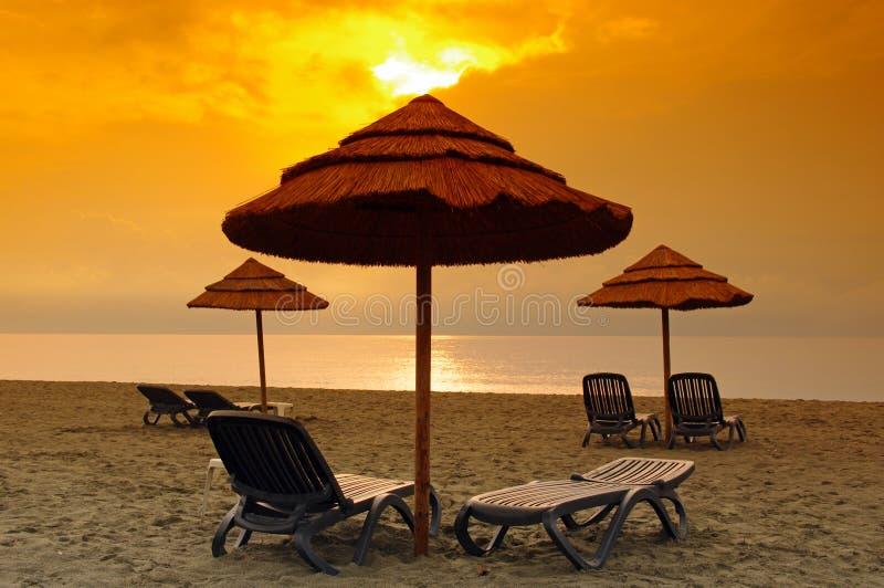 Deckchair ed ombrello in spiaggia della Corsica immagine stock libera da diritti
