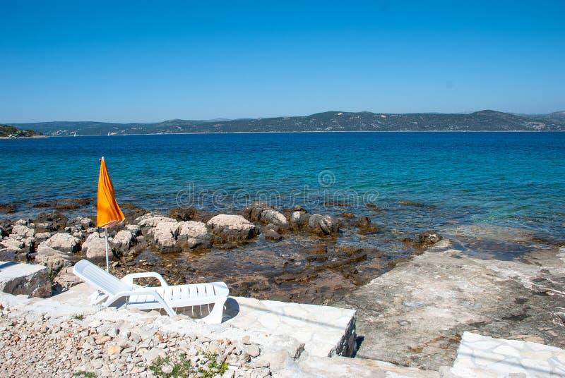 Deckchair em uma praia rochosa foto de stock