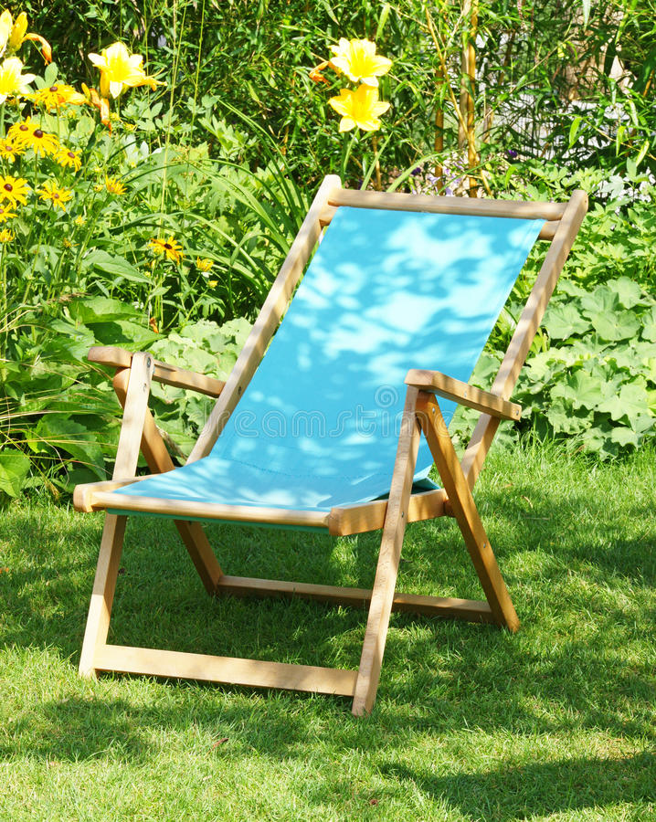 Deckchair in garden. Traditional wooden deckchair on lawn in garden with flowers in background stock image