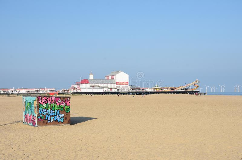 Deckchair Hire hut on Beach at Great Yarmouth with pleasure pier in background and graffitti hut at front. Great Yarmouth Norfolk , United Kingdom - October 25 royalty free stock photo