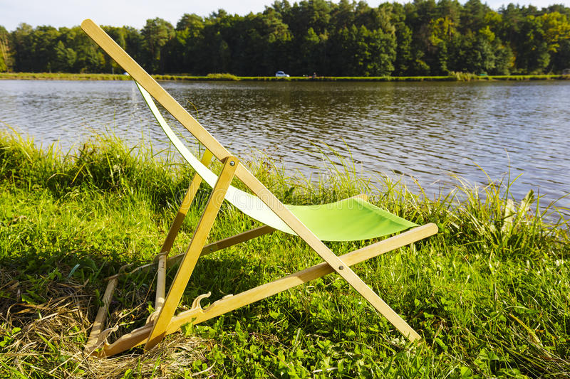 Deckchair at the lake. The empty deckchair stands on the grass at the edge of the lake royalty free stock photos