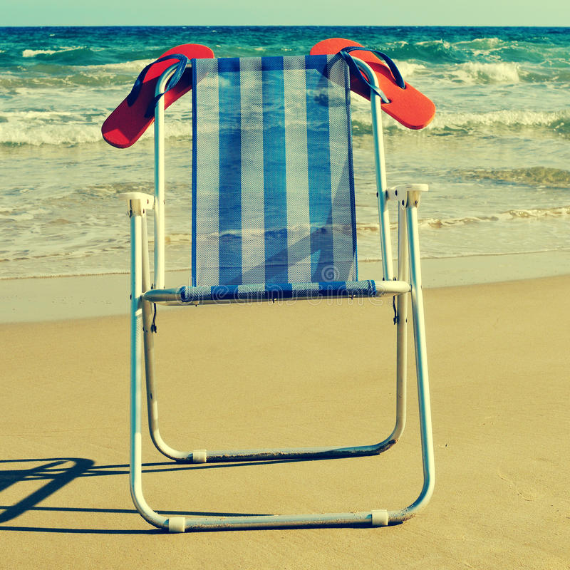 Deckchair and orange flip-flops on the beach, with a retro effect. A deckchair with a pair of orange flip-flops on the beach, with a retro effect stock photos